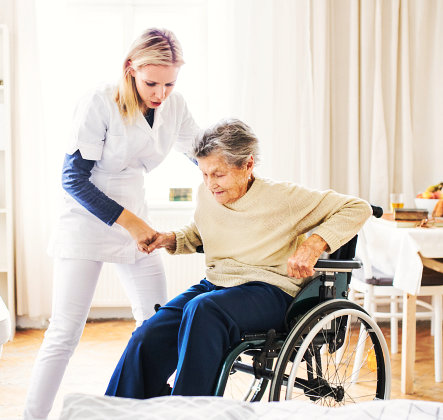 caregiver asisssting senior woman to stand up