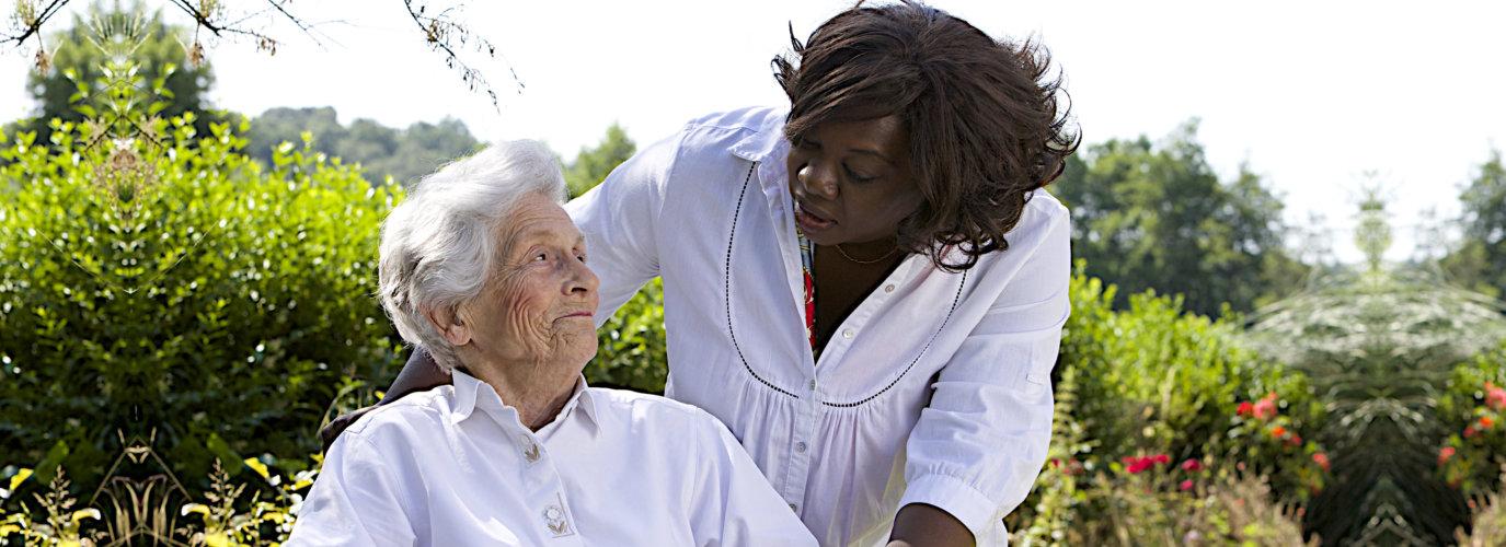 senior woman and caregiver having a walk outdoor