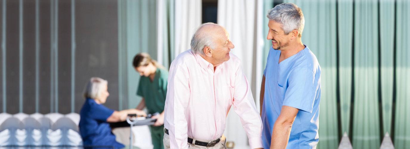 Happy male caretaker looking at disabled senior man at nursing home yard