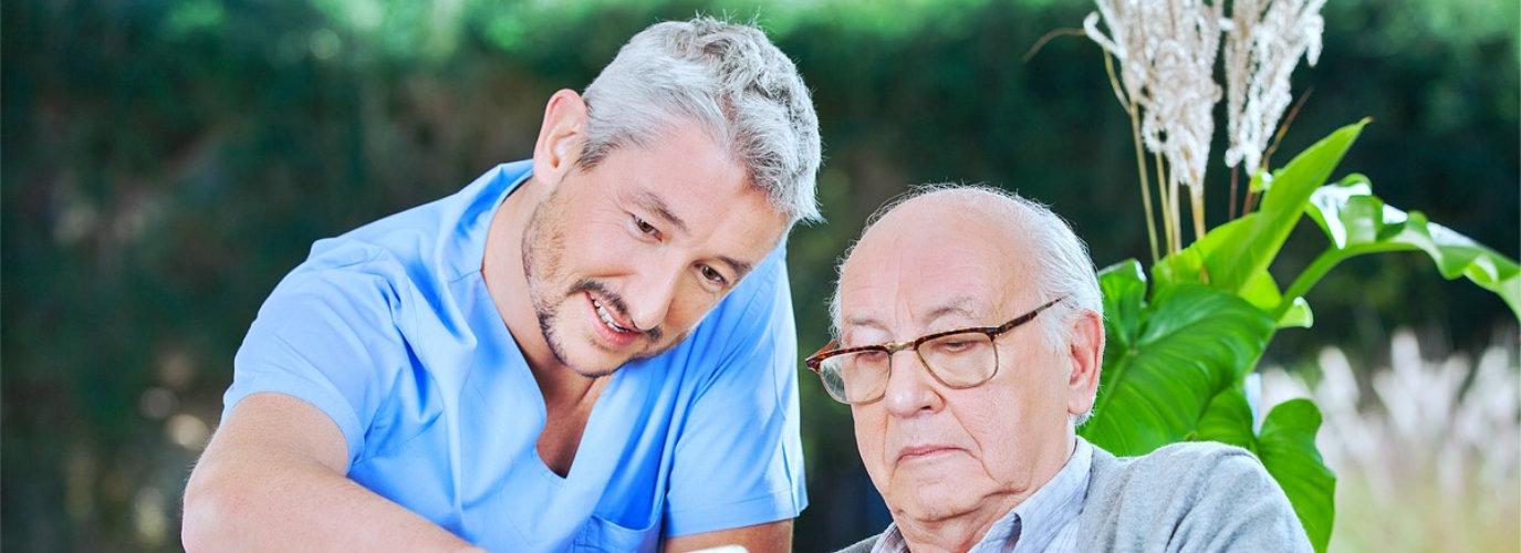 caregiver and senior man using tablet