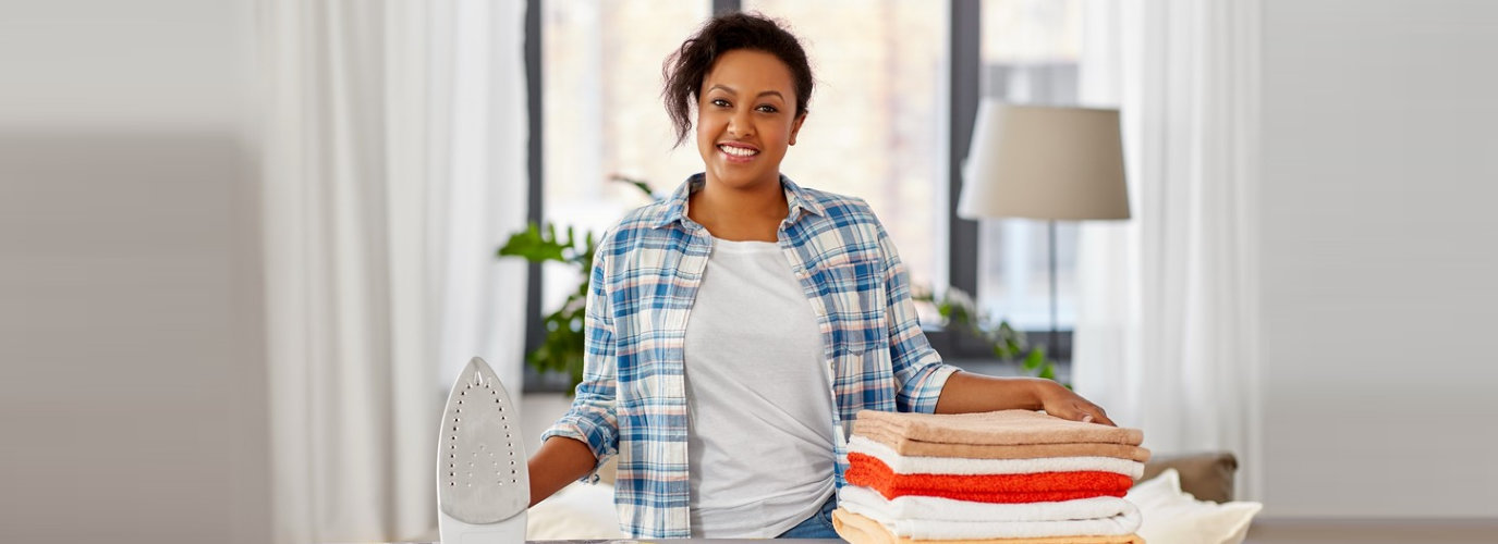 smiling caregiver ironing the clothes
